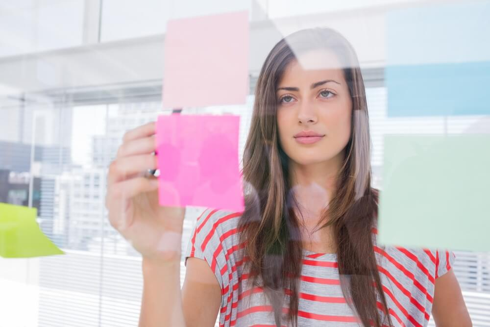 woman arranging sticky notes into a customer journey map